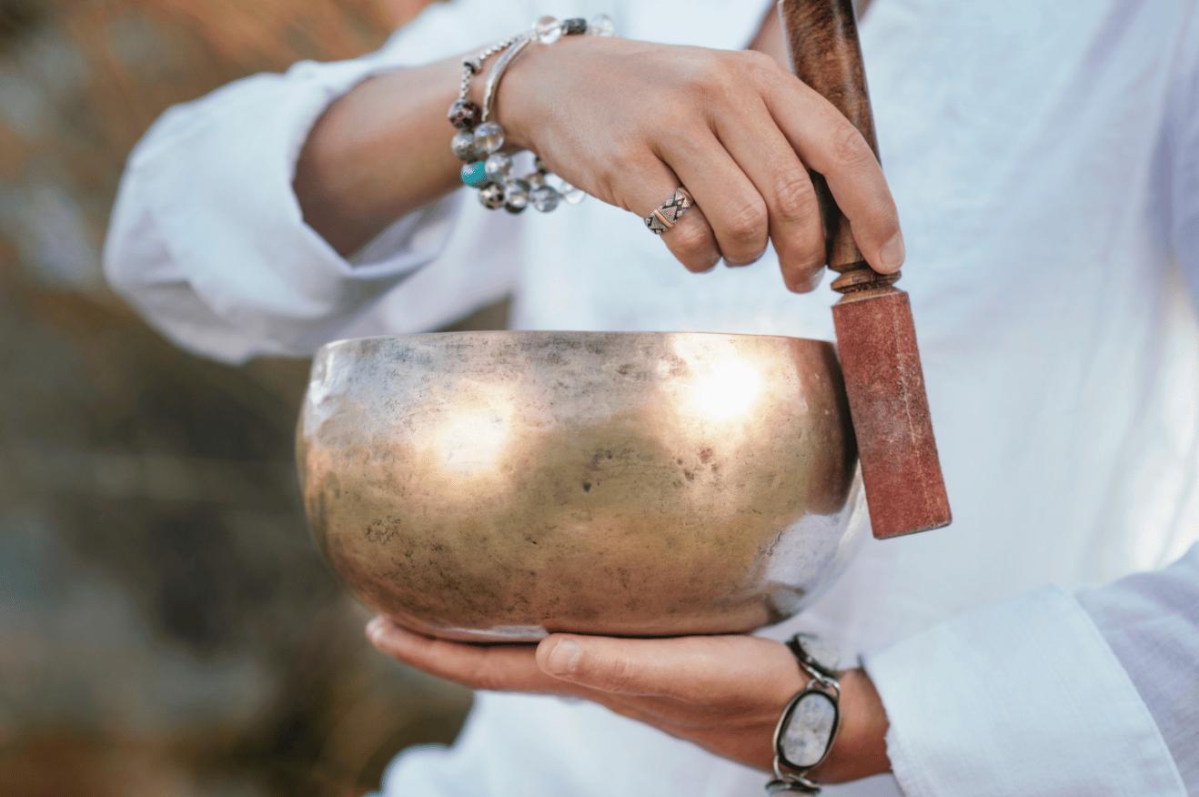 Frapper le bol tibétain pour le faire chanter